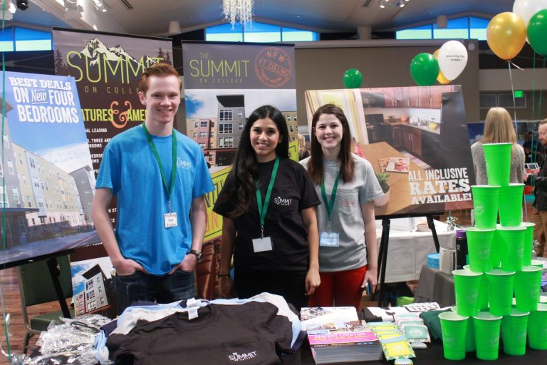 Three people standing in front of a booth at the housing fair