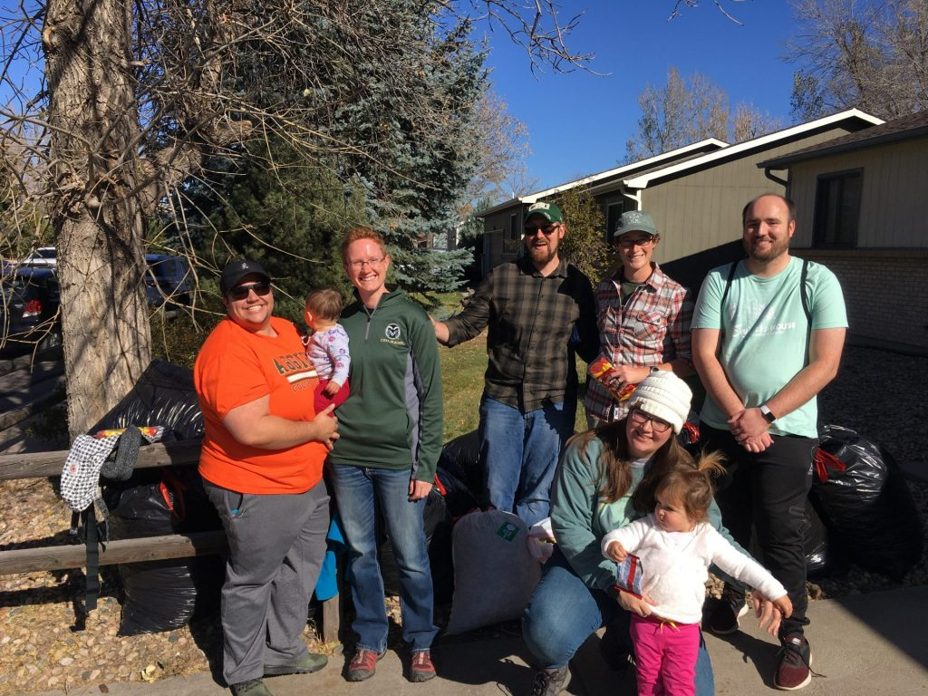A fall clean-up group standing in front of a house they finished, smiling at the camera