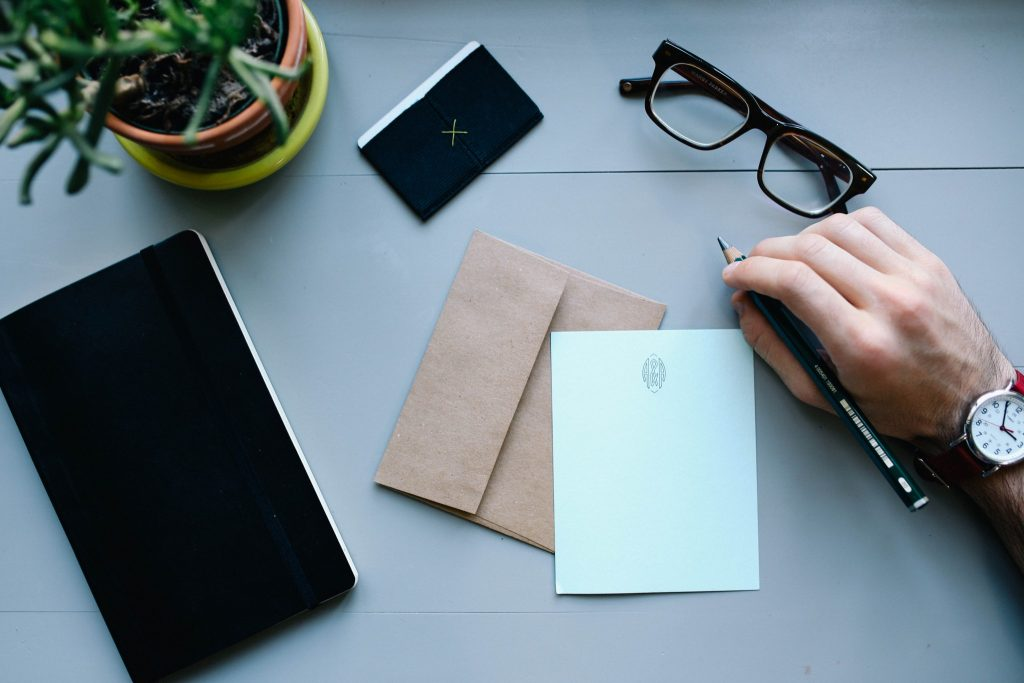 A stock photo of glasses, a hand holding a pen, and an envelope