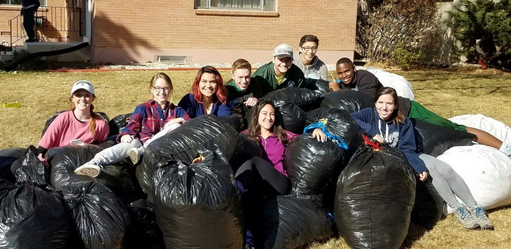 A fall clean-up team sitting among all the bags of leaves they picked up
