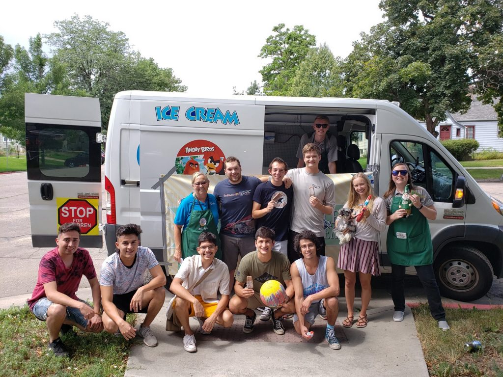 Get the scoop volunteers standing in front of the ice cream truck