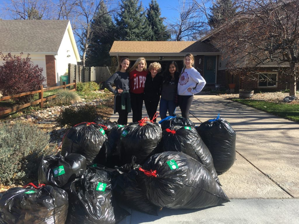 A fall clean-up team standing in front of a pile of bags of leaves